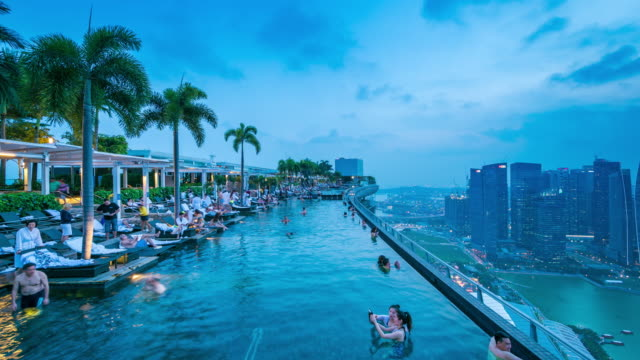 timelapse of marina bay sands pool at nightfall, singapore - marina bay sands stock videos and b-roll footage