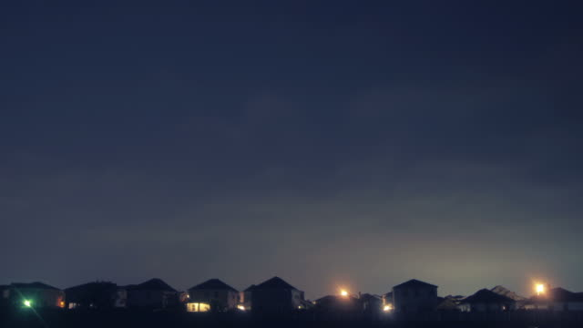 Timelapse of morning dawning above the houses of a subdivision