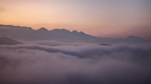 Time-lapse of mountain and moving mist at sunrise time