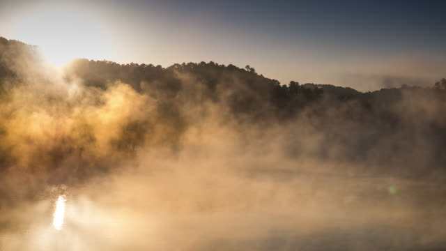 Time-lapse of moving mist on the Reflection lake with sunrise in the morning , 4k (UHD)