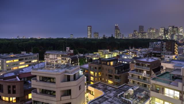 vídeos de stock, filmes e b-roll de timelapse of nightfall on yoyogi park from harijuku, tokyo - distrito residencial