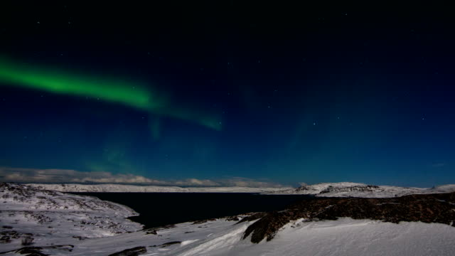 timelapse of northern lights over the mountains and the sea - polarlicht stock-videos und b-roll-filmmaterial
