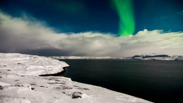 vídeos de stock e filmes b-roll de timelapse of northern lights over the mountains and the sea - norte