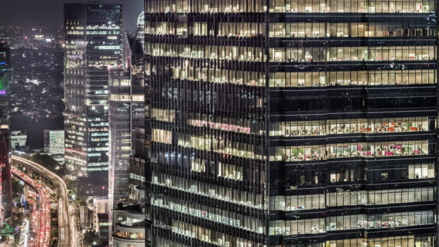 timelapse of office building and busy road at night