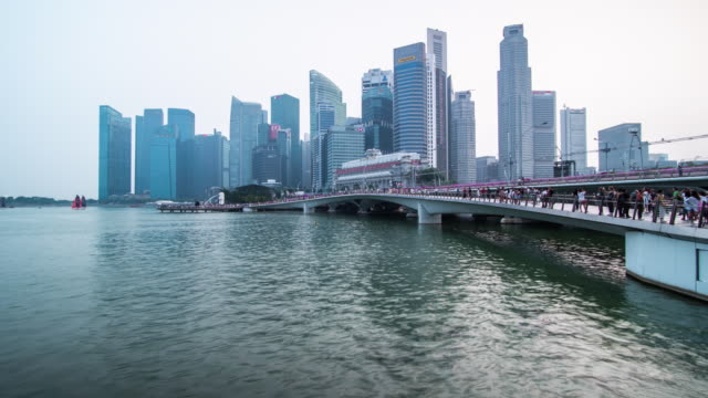 timelapse of pedestrian walkway around marina bay in singapore - river singapore stock videos & royalty-free footage