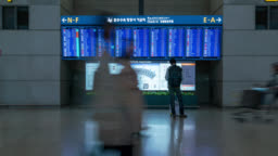 Timelapse of people in international airport terminal, looking at information board, checking flight.