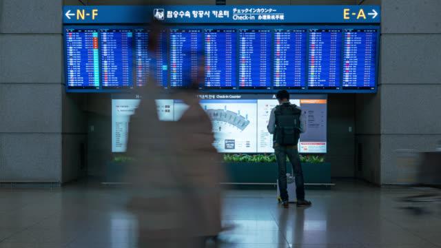 zeitraffer von menschen im flughafenterminal, mit blick auf informationstafel, check-flug. - passagierflugzeug stock-videos und b-roll-filmmaterial