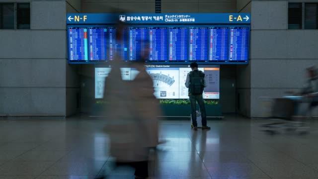 zeitraffer von menschen betrachten boarding-zeit in saubere stadt seoul incheon international airport, südkorea - arrival stock-videos und b-roll-filmmaterial