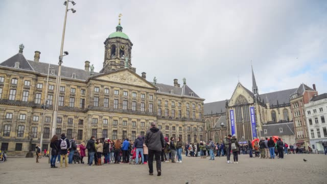 timelapse of people moving in front of famous royal palace in dam square, amsterdam, capital of netherlands, europe - town hall stock videos & royalty-free footage