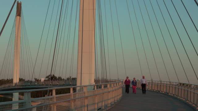 Timelapse of people walking on John Kerry Pedestrian Bridge over Missouri River at sunset