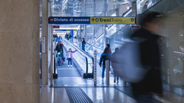 timelapse of poeple use escalator to underground store in subway station milan italy - stazione video stock e b–roll
