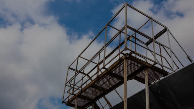 timelapse of rusty steel walkway framing passing clouds. - elevated walkway stock videos & royalty-free footage