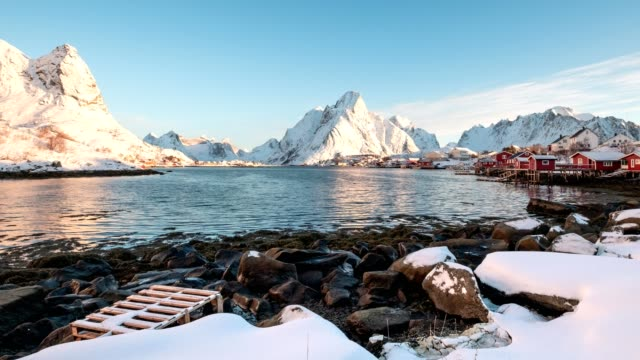 Time-lapse of Scandinavian village in snowy mountain range with blue sky on coastline at Lofoten islands
