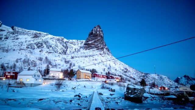 zeitraffer des skandinavischen dorfes mit aurora borealis im verschneiten tal an küste - polarlicht stock-videos und b-roll-filmmaterial