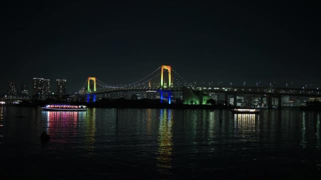 timelapse of ships sailing past an illuminated rainbow bridge at night in tokyo, japan, on wednesday, dec. 20, 2016 - ナイトイン点の映像素材/bロール