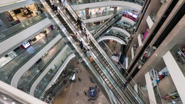 timelapse of shoppers using escalator inside busy shopping mall