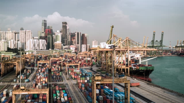 T/L timelapse of Singapore's cargo and container port infront of the financial district and skyline