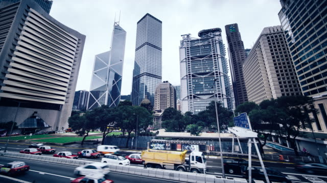 time-lapse of skyscrapers of central district, hong kong under grey sky - bank of china tower hong kong stock videos and b-roll footage