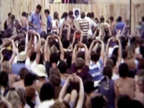 stockvideo's en b-roll-footage met timelapse of stage being set up and crowd arriving, people stretching, helicopter arrives, richie havens begins to play. super 8mm home movie footage. - festivalganger