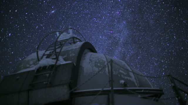 timelapse of starry night sky over observatory - inquadratura fissa video stock e b–roll