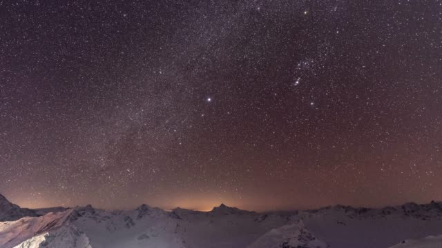 timelapse of starry night sky over snowy mountain landscape in the caucasus - star field stock videos & royalty-free footage