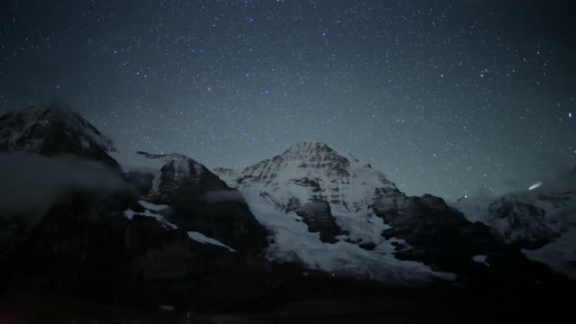 "timelapse of starry sky and clouds, swiss alps - ""bbc universal"" stock-videos und b-roll-filmmaterial"