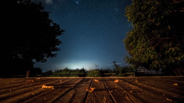 time-lapse of stars clouds and planes framed by trees from a wooden deck - patio stock-videos und b-roll-filmmaterial