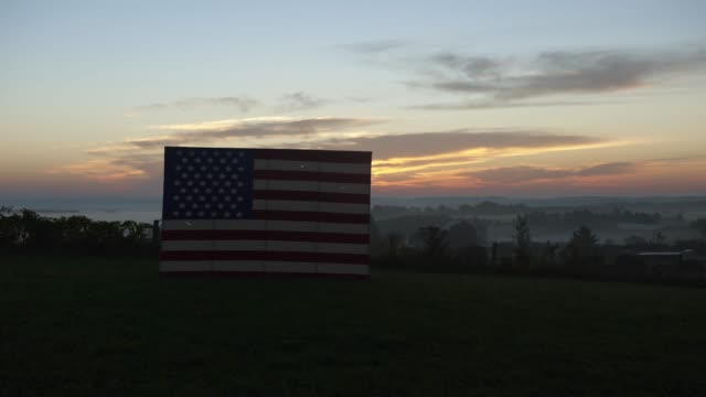stockvideo's en b-roll-footage met time-lapse of sun rising over american flag - boerderijschuur