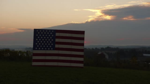 time-lapse of sun rising over american flag - amerikanischer treueschwur stock-videos und b-roll-filmmaterial