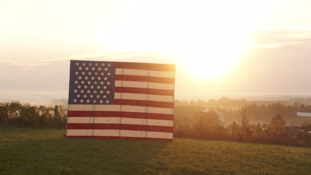 Time-lapse of sun rising over American flag