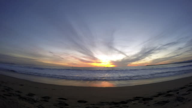 Time-lapse of sun setting at the beach over ocean horizon.   - Time-Lapse