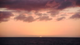 Timelapse of sun setting on horizon over the ocean during  orange and pink sunset