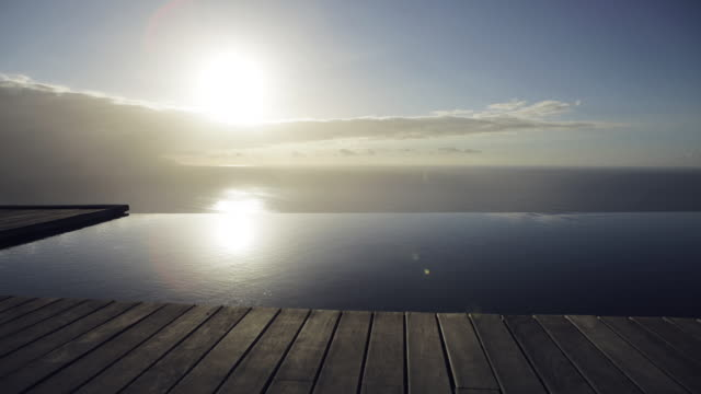 timelapse of sun setting over infinity pool and ocean - infinity pool stock videos & royalty-free footage