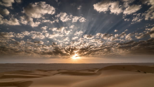 Timelapse of sunrise and clouds moving over desert landscape