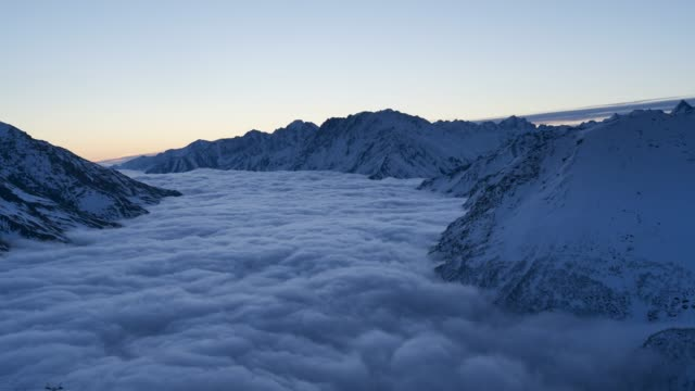 timelapse of sunrise over sea of clouds and fog over high mountain peaks - winter stock videos & royalty-free footage