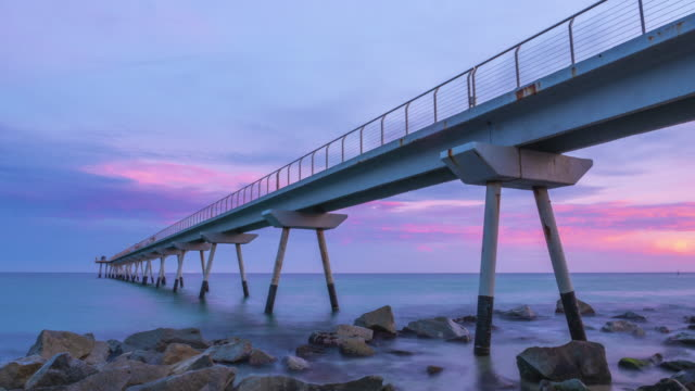"timelapse of sunset landscape of boardwalk in the beach in badalona (barcelona) ""pont del petroli"" - pier stock videos & royalty-free footage"