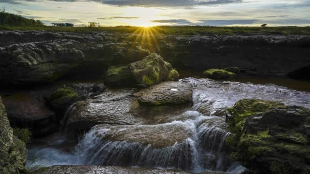time-lapse of sunset over a water stream through rocks. - ネイチャーズウィンドウ点の映像素材/bロール