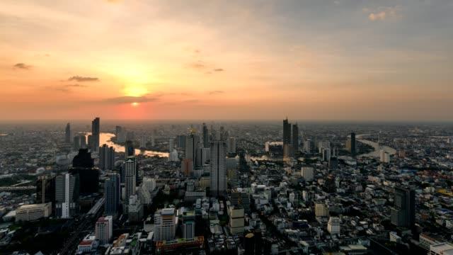 vídeos de stock, filmes e b-roll de lapso de tempo do pôr do sol sobre a cidade de banguecoque, com semáforo na tailândia - alto descrição geral