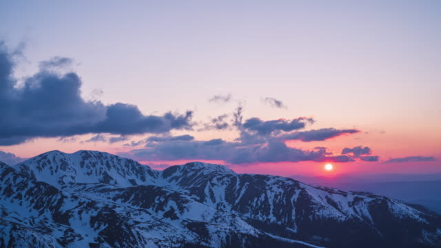 timelapse of sunset over snowy mountains - mountain stock videos & royalty-free footage