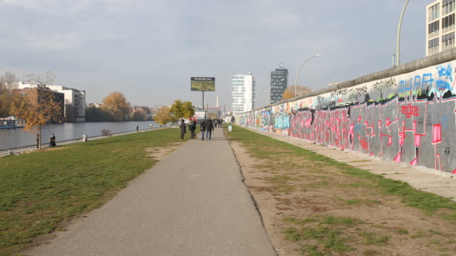 timelapse of the actual berlin wall at the back side of the east side gallery at the spree river and its famous graffiti paintings in a sunny autumn... - river spree stock videos & royalty-free footage