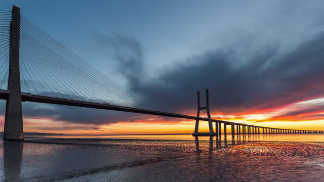 timelapse of the beautiful sunrise over the vasco da gama bridge. lisbon, portugal. april, 2017. - cable stayed bridge stock videos & royalty-free footage