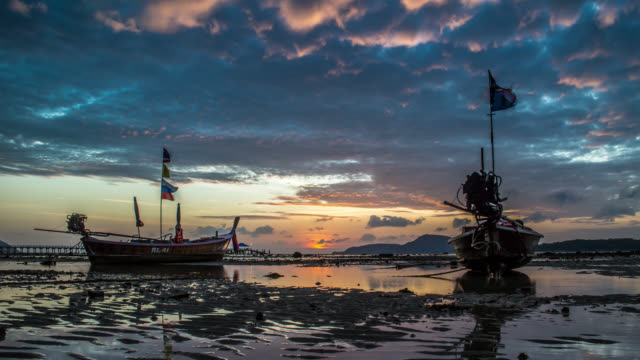 vídeos de stock, filmes e b-roll de timelapse of the beautiful sunrise with long-tail boats in low water during high tide,thailand. january, 2016. - vazante