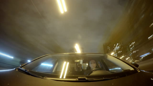 timelapse of the car at night on a city street. man driving. front view from the car body - フロントガラス点の映像素材/bロール
