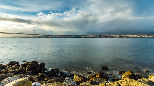 timelapse of the clouds over the lisbon skyline, 25th of april bridge and tagus river. portugal. april, 2017 - 4月25日橋点の映像素材/bロール