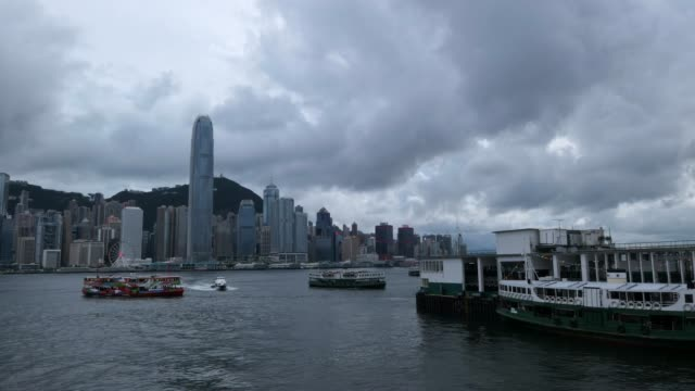 vidéos et rushes de timelapse of the iconic city skyline of hong kong with busy ships navigates along victoria harbour on a gloomy day - établissement financier