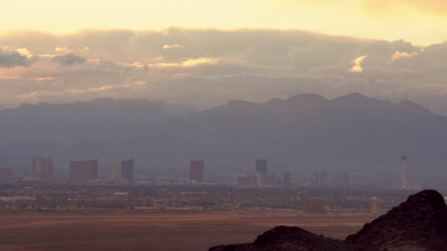 a time-lapse of the las vegas skyline around sunset with a storm hanging over the mountains - las vegas stock videos & royalty-free footage