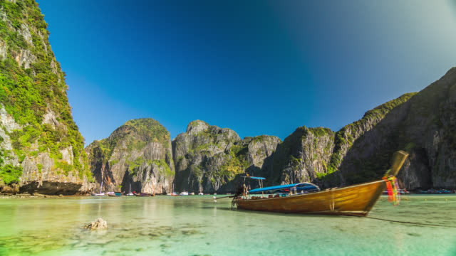 timelapse of the maya bay beach with long-tail boats on phi phi ley island, thailand. january, 2016. - inselgruppe phi phi stock-videos und b-roll-filmmaterial