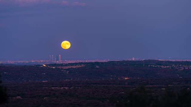 timelapse of the moon rising behind the four towers in madrid - supermoon stock videos & royalty-free footage