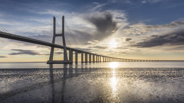 timelapse of the morning sun over the vasco da gama bridge. lisbon, portugal. april, 2017. - cable stayed bridge stock videos & royalty-free footage