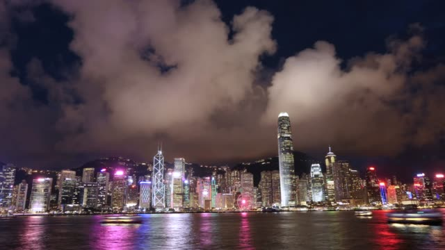 timelapse of the multi-coloured and illuminated night view of the iconic city skyline of hong kong with busy ships navigates along victoria harbour at night - star ferry stock videos & royalty-free footage